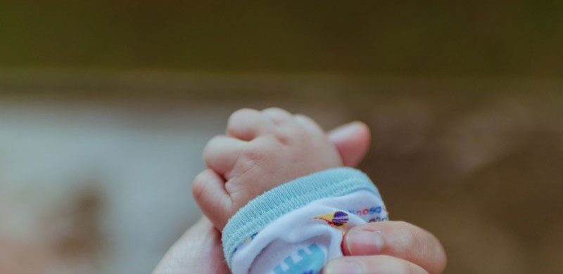 baby holding parent's hand