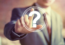 suited man pressing question mark icon